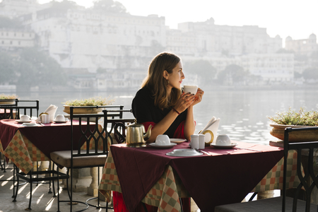Western woman having a teatime at a cafe in Udaipur Stock Photo - 113891439
