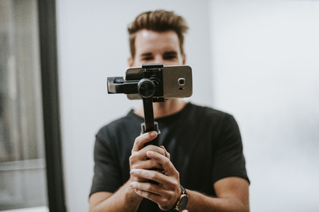 Man holding a gimbal with a phone 스톡 콘텐츠 - 113891459