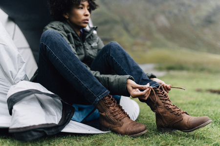 Woman tying her shoelaces by her tent Stock Photo