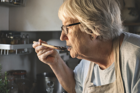 Senior woman preparing dinner in the kitchen 스톡 콘텐츠 - 113891500