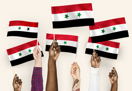 Hands waving flags of Syria