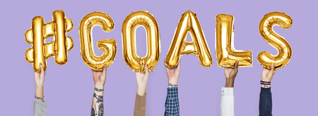 Hands holding #goals word in balloon letters