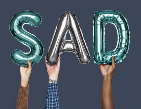 Hands showing sad balloons word