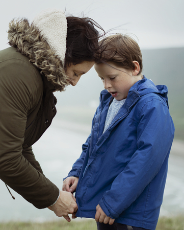 Mother helping her son to zip his jacket Stock Photo