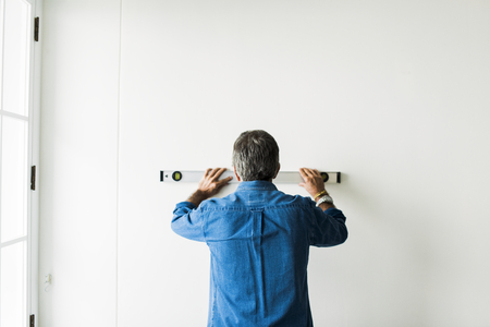 Man using a spirit level on a wall Stock Photo - 113891643