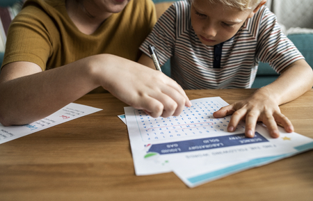 Sister playing word search with her little brother