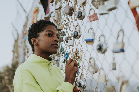 Woman by a fence with padlocks in LA Banco de Imagens