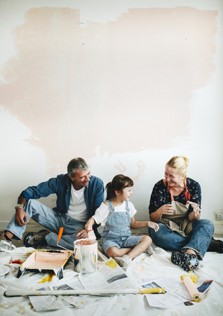 Cheerful family relaxing after painting the walls Stockfoto