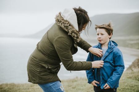 Mother helping her son zip his jacket