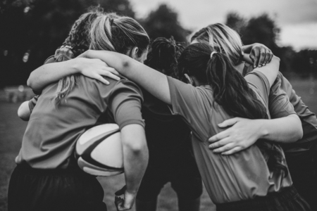 Young female rugby players huddling Imagens