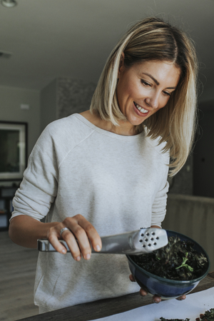 Woman serving fried kale and chickpeas