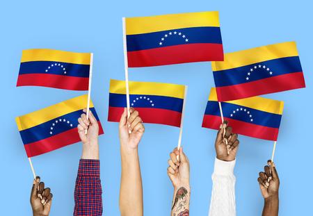 Hands waving flags of Venezuela Stock Photo