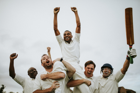 Cheerful cricketers celebrating their victory Imagens
