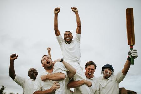 Giocatori di cricket allegri che celebrano la loro vittoria