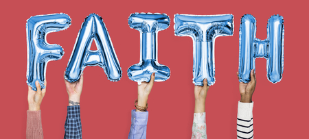 Hands holding faith word in balloon letters Stock Photo