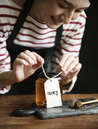 Woman packing organic honey into a jar