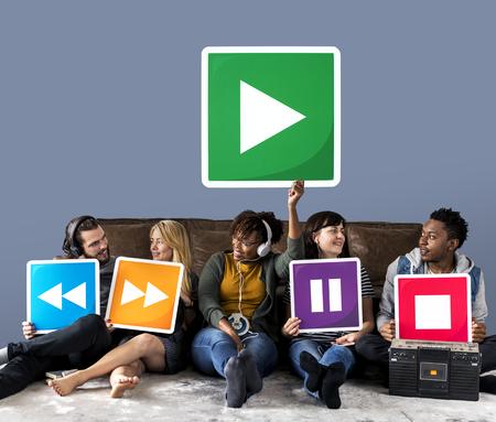 Persone che tengono le icone del lettore multimediale e un'icona di riproduzione