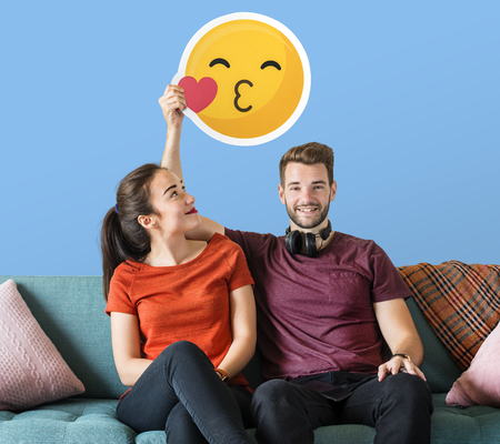 Cheerful couple holding a kissing emoticon