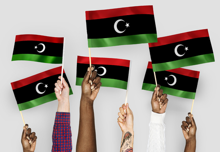 Hands waving flags of Libya 스톡 콘텐츠 - 113918337