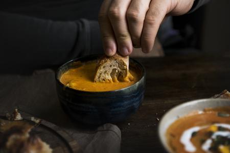 Man eating a creamy pumpkin soup