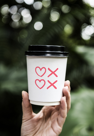 Hearts and kisses symbols on a paper coffee cup