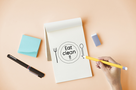Hand writing Eat clean on a notepad