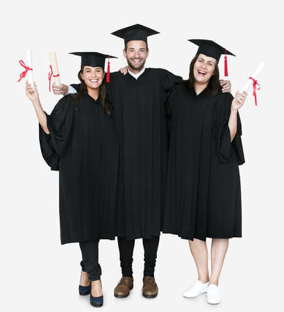 Group of grads in cap and gown holding diplomas