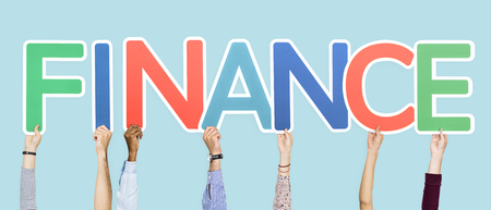 Hands holding up colorful letters forming the word finance