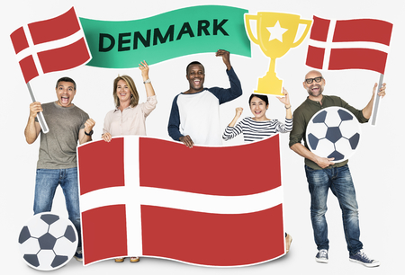 Diverse football fans holding the flag of Denmark 스톡 콘텐츠