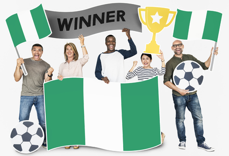 Diverse football fans holding the flag of Nigeria