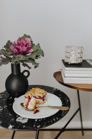 Slice of cheesecake next to an ornamental kale on a black table Stock fotó - 113955977