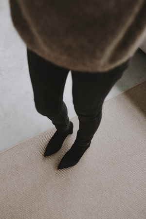 Woman in ankle boots standing in her house Фото со стока