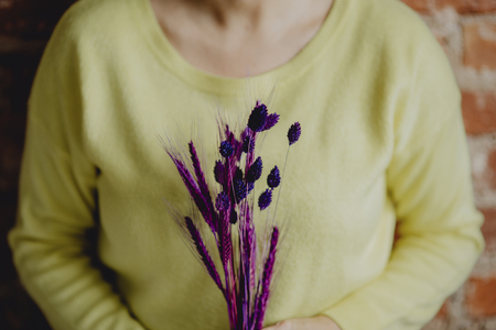 Woman holding a bundle of purple dyed wheat 写真素材