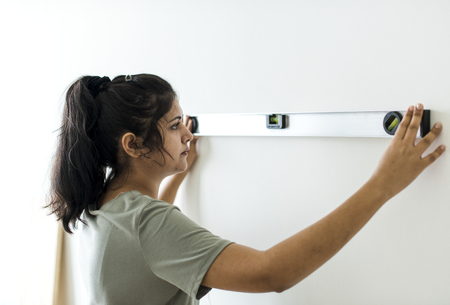 Woman using a spirit level on a wall