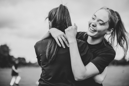 Female football players hugging each other