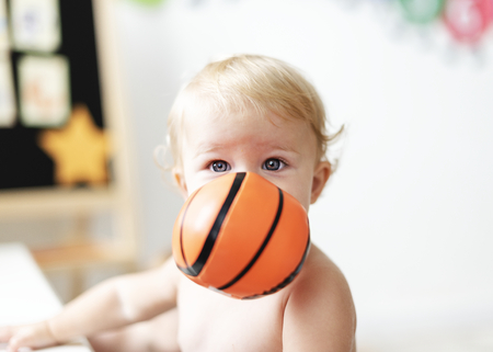 Baby playing with a basketball toy