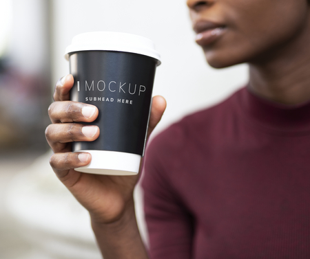 Woman drinking coffee out of a paper cup mockup