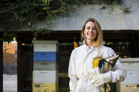 Beekeeper in front of her bee hives