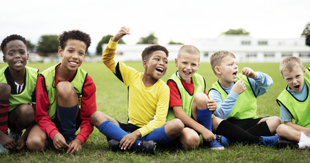 Enthusiastic football players sitting on the field