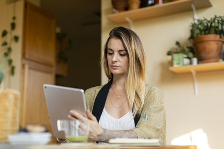 Relaxed woman working from home on her tablet Stock Photo