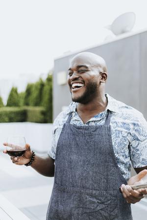 Cheerful chef enjoying a wine of glass