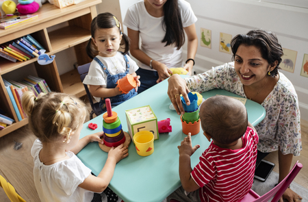 Nursery children playing with teacher in the classroom Imagens - 115668764