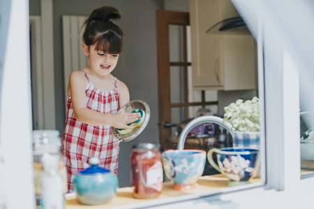 Little girl doing the dishes