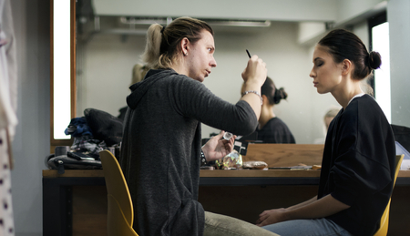 Makeup artist applying makeup onto model