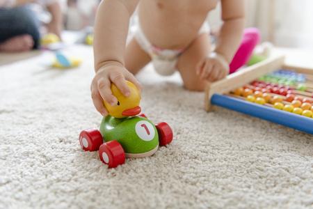 Baby spielt mit einem Holzauto
