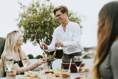 Man serving his friends salad at a rooftop party