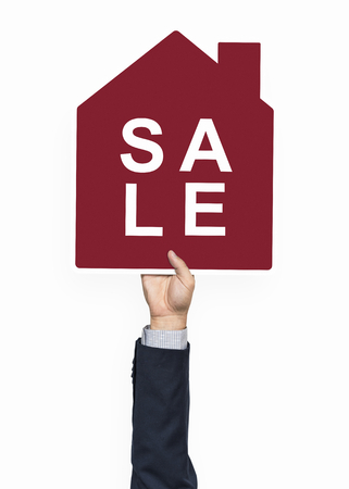 Hand holding a house for sale Stock Photo