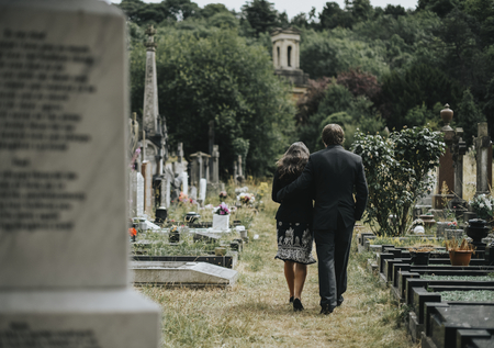 Sad couple walking through a cemetery Stock Photo