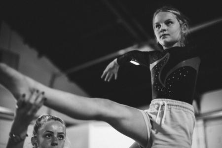 Coach die jonge turnster opleidt om op een evenwichtsbalk te balanceren