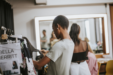 Stylist selecting clothes for a model